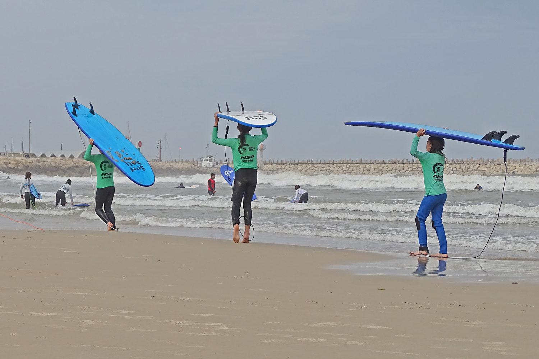 ילדים הולכים בחוף עם גלשנים